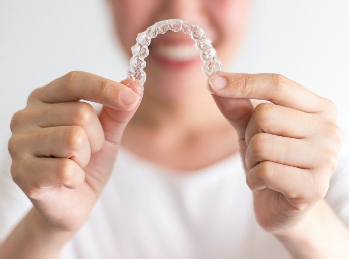 kelowna orthodontist young-woman-holding-invisalign-westside-orthodontic-centre