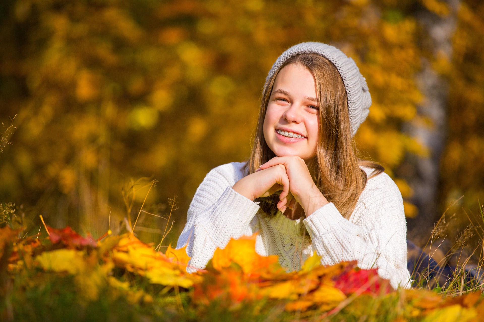 Teenage girl with braces in park in autumn